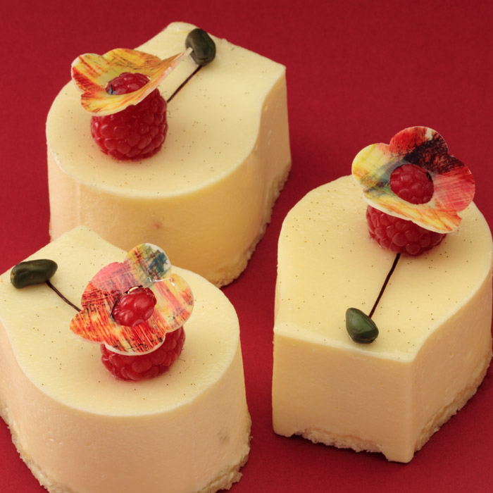 3 small 'Splendor' cakes decorated with raspberries and white chocolate flowers