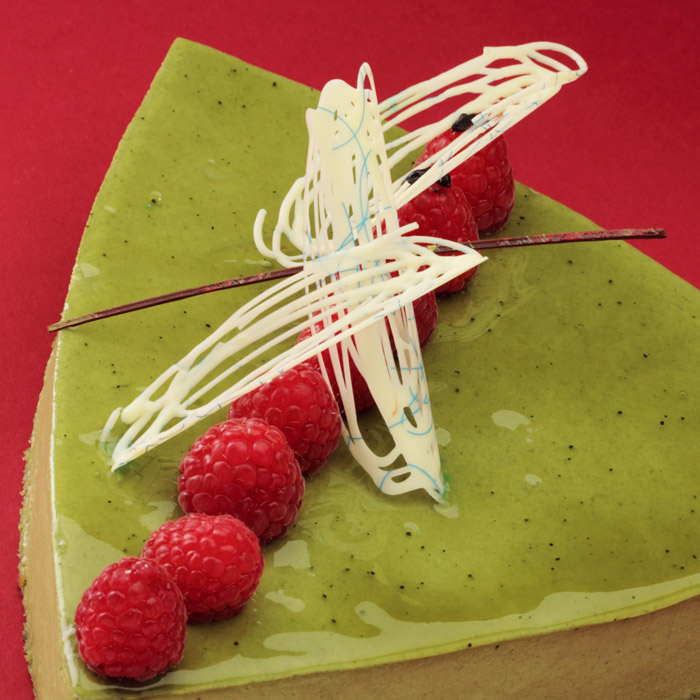 A slice of our Green Tea Kilo cake topped with white chocolate swirls and raspberries